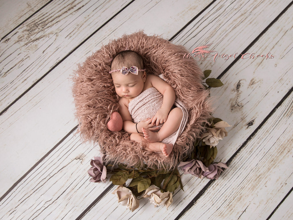 all wrapped newborn baby in a basket all wrapped in dusky pink with roses